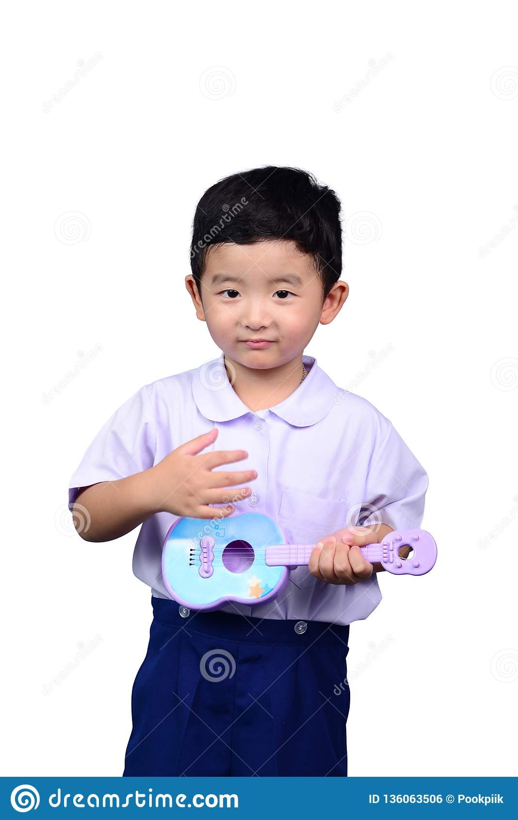 Asian Thai kindergarten student kid in school uniform playing toy guitar isolated on white background with clipping path. musical