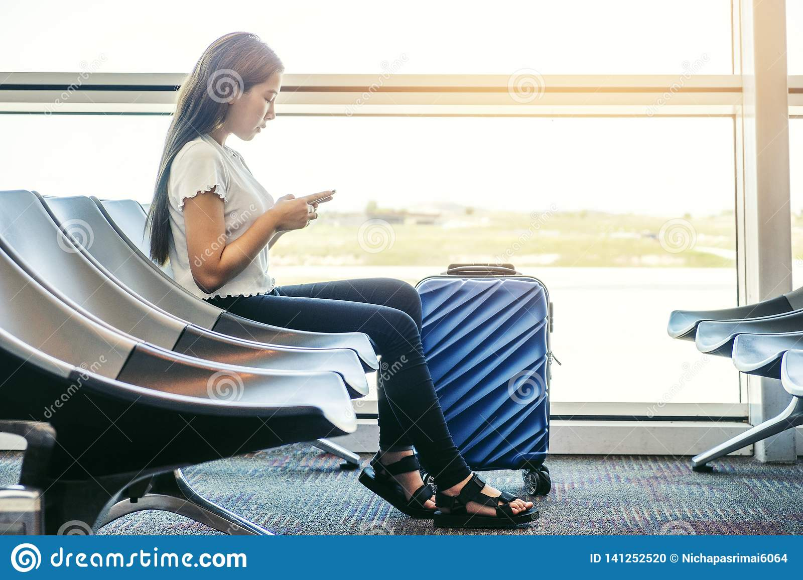 Asian Traveler women looking for flight in smartphone at airport terminal Travel concept