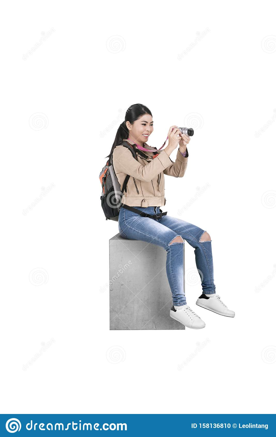 Asian woman with a backpack sitting and holding a camera to take pictures