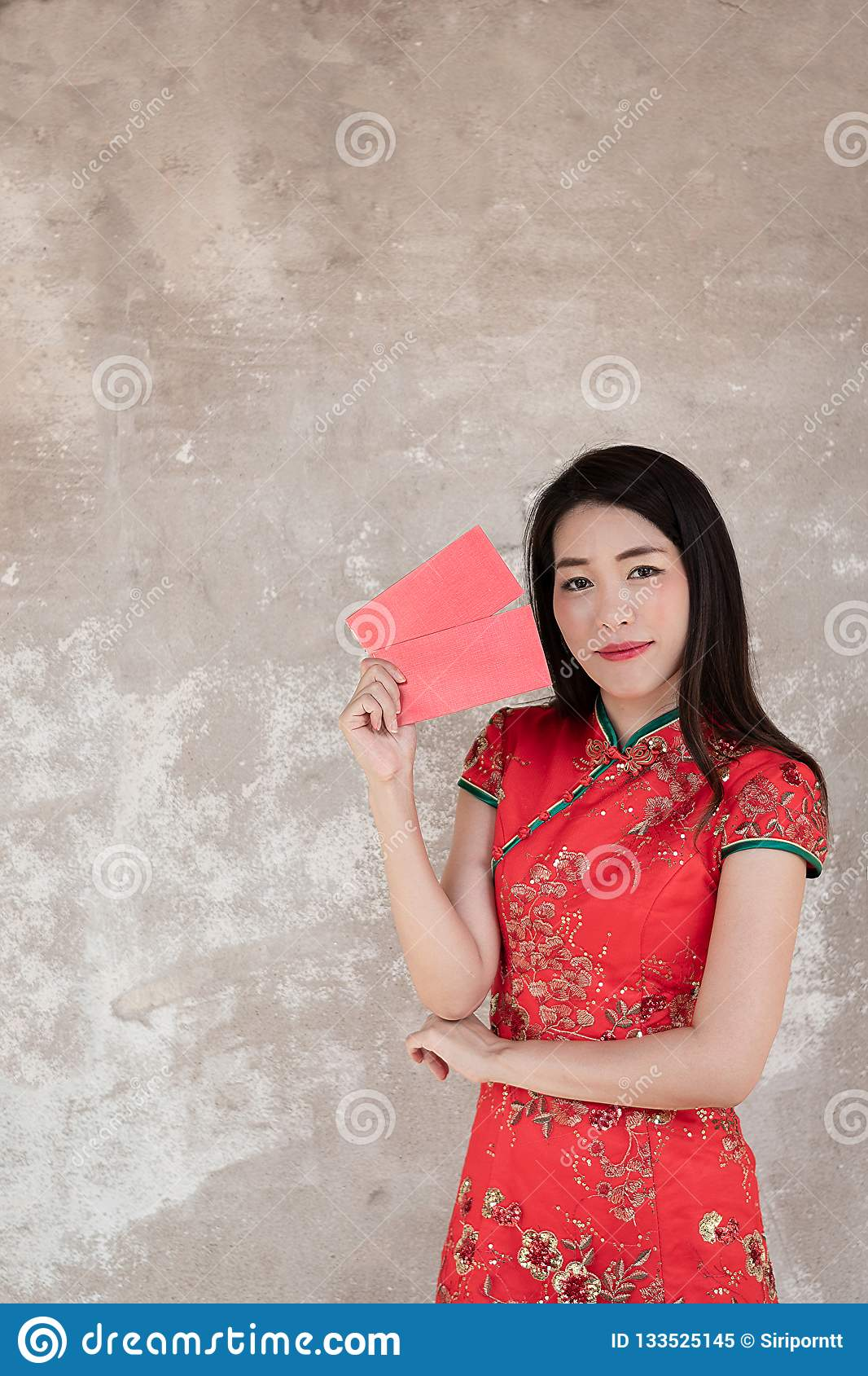 13338a0ed9c6 Asian woman in chinese dress traditional cheongsam holding red pocket  evelop on white textured background with copy space