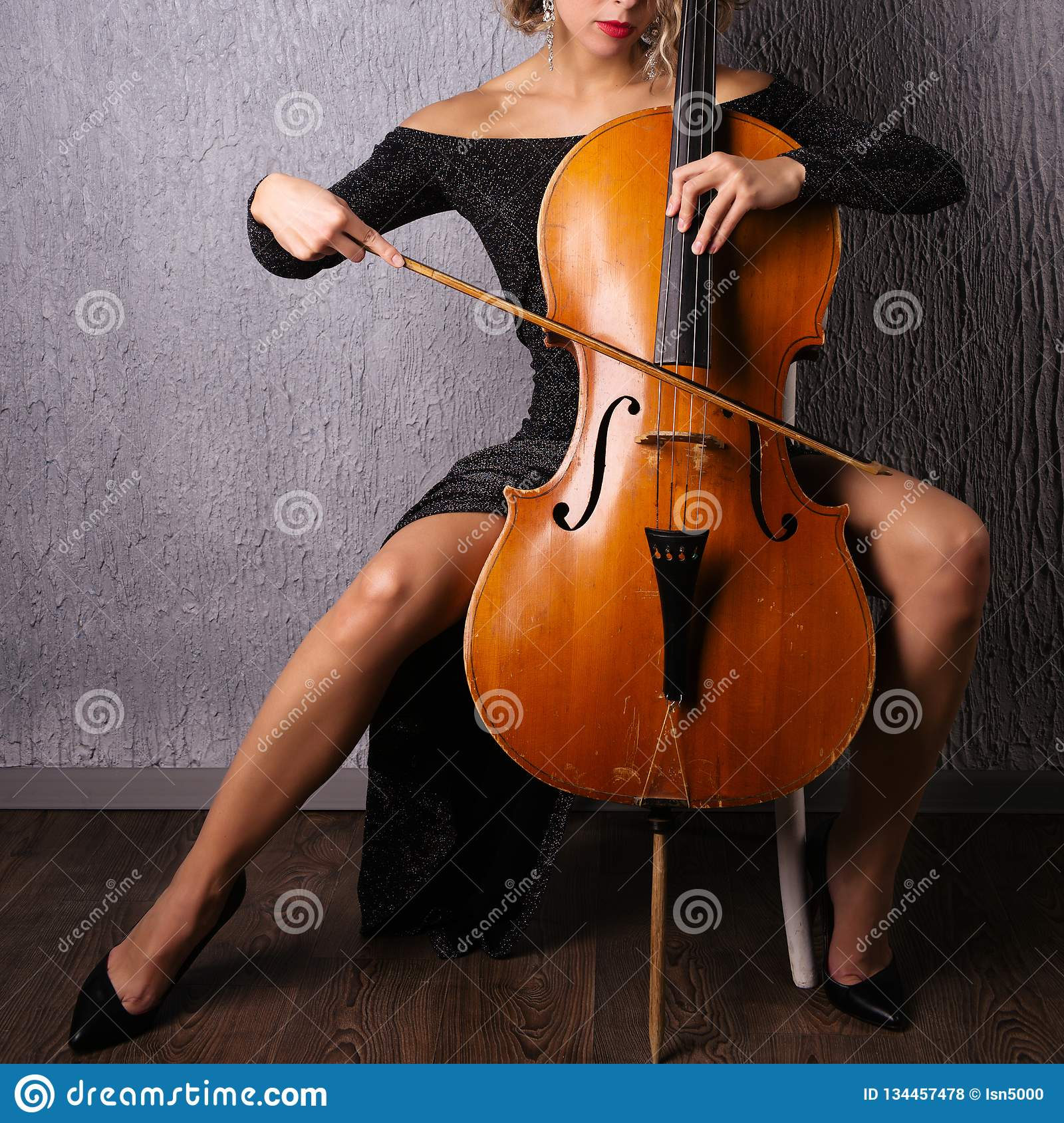 Asian woman in an evening dress playing the cello