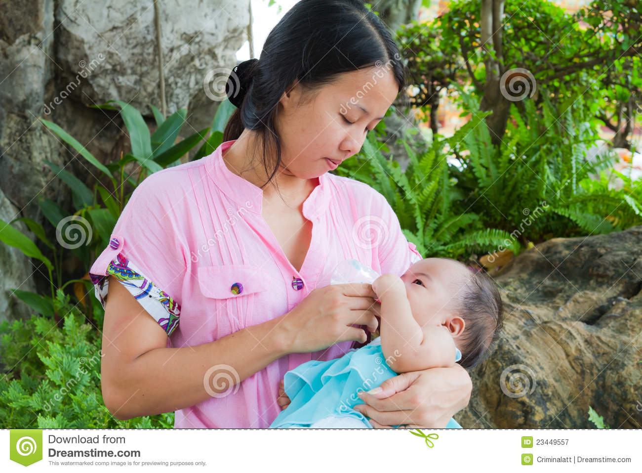 Asian woman feeding her baby in park