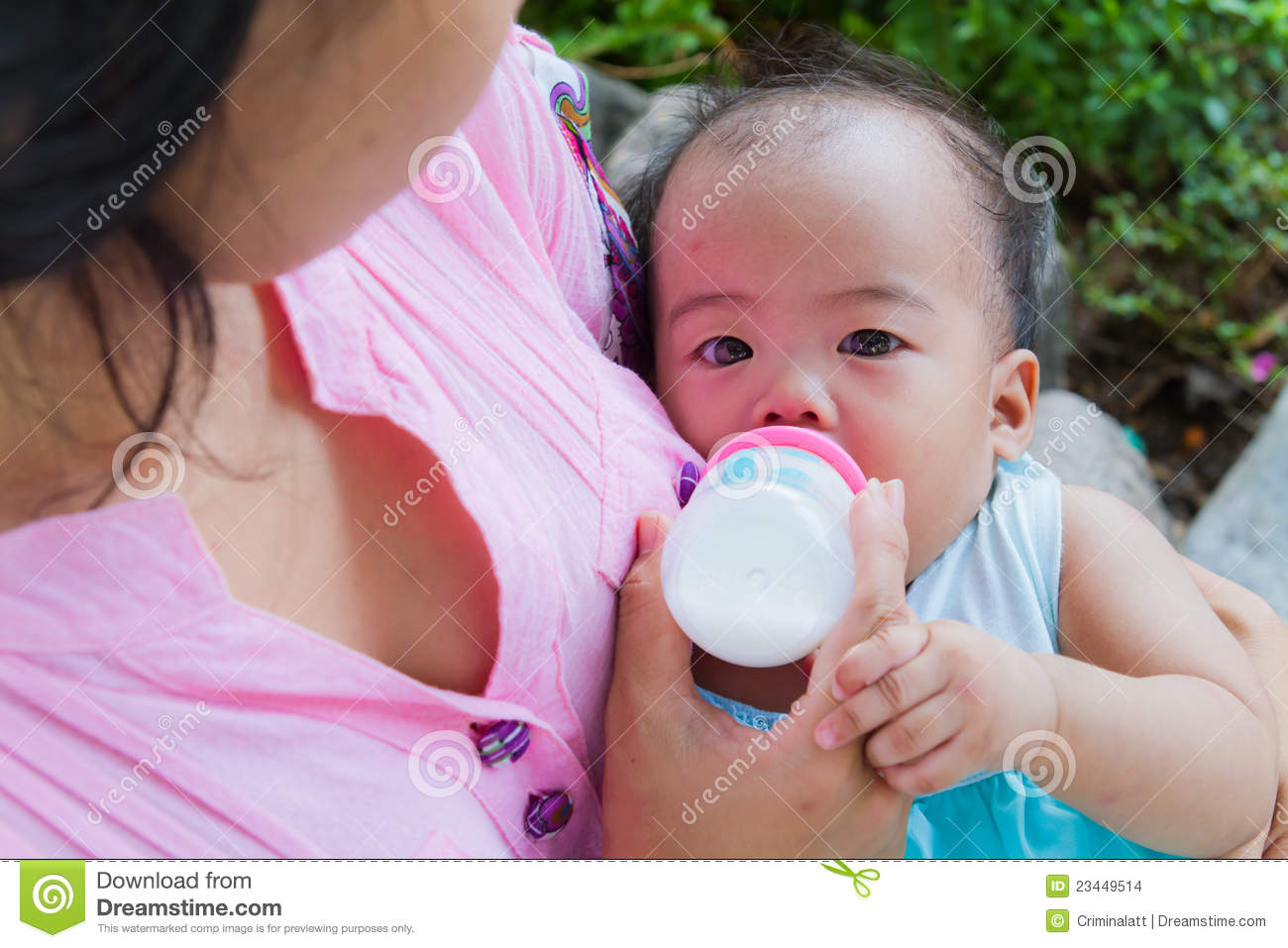 Asian woman feeding her baby from top