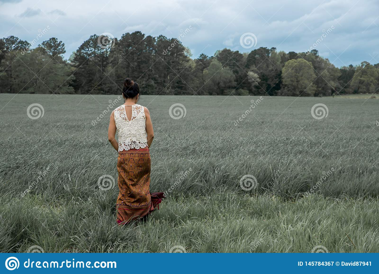Asian woman in field surrounded by grass