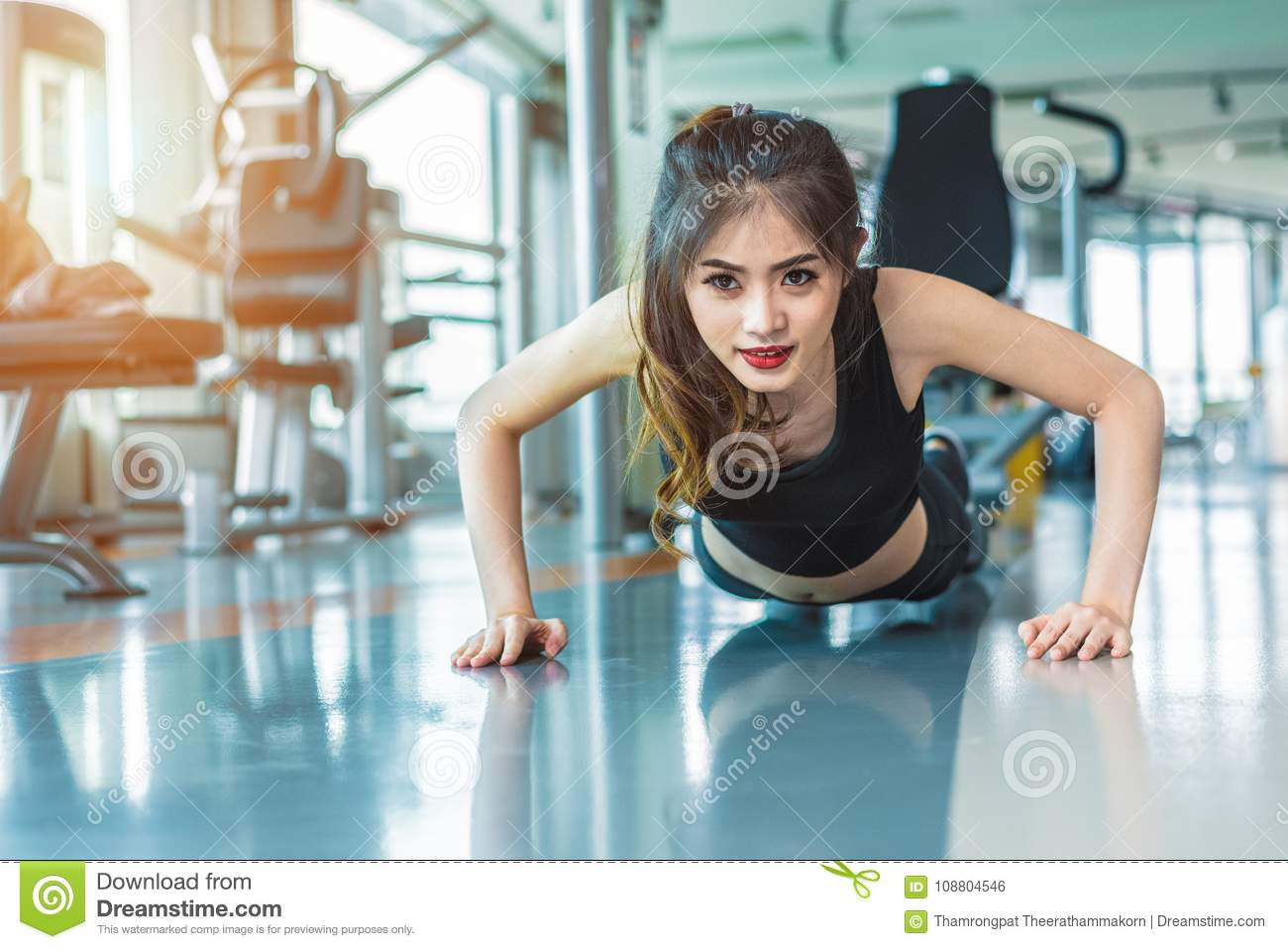 Asian woman fitness girl do pushing ups at fitness gym. Healthcare and Healthy concept. Training and Body build up theme.