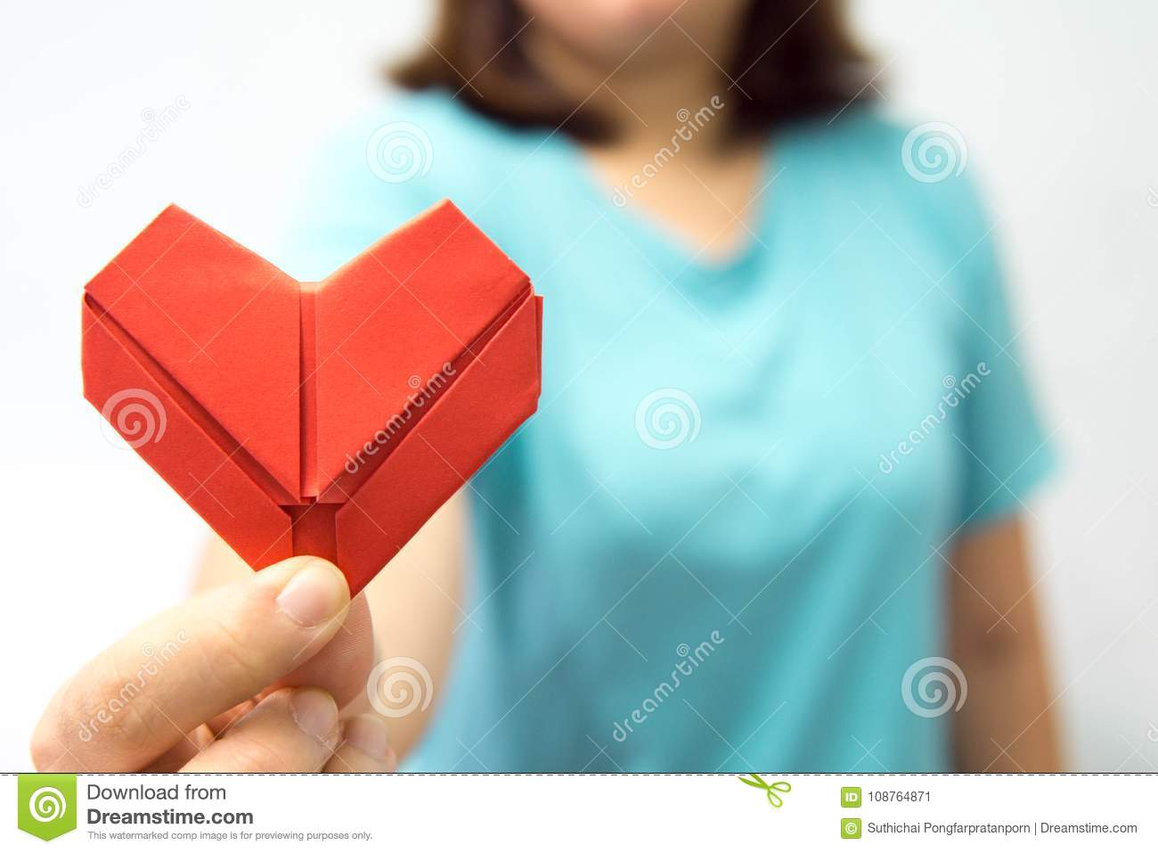 An asian woman holding heart origami in front of her chest. A woman giving red heart paper to someone. Love and give concept for v