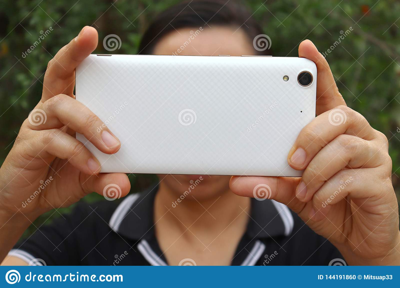 Asian woman holding and using smart phone show back side