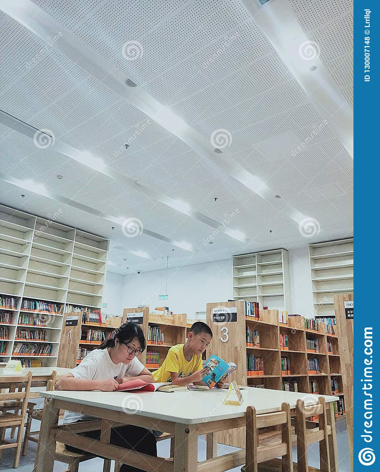 An Asian woman and a little boy who are reading