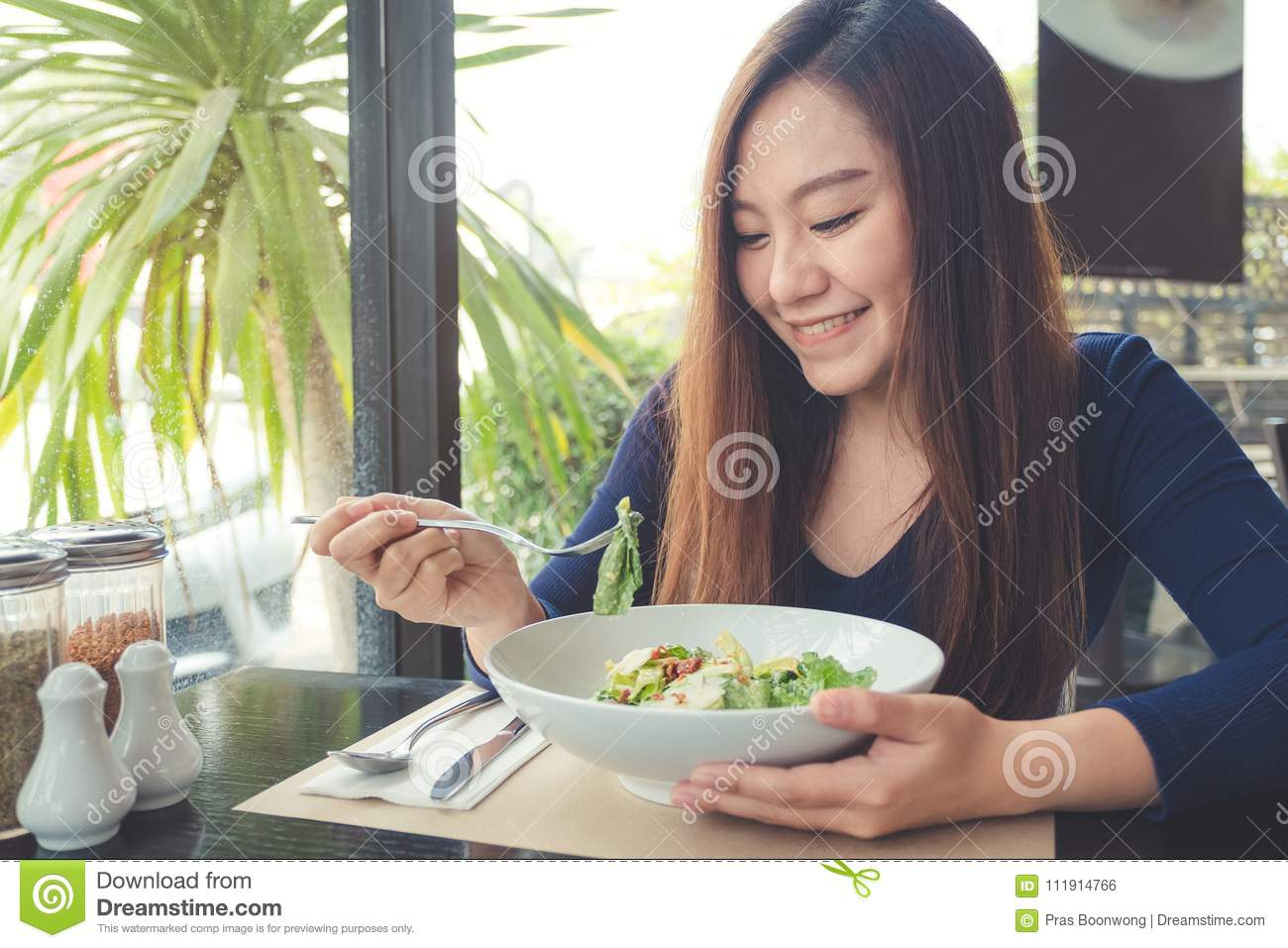 An Asian woman looking and enjoy eating Ceasar salad in restaurant