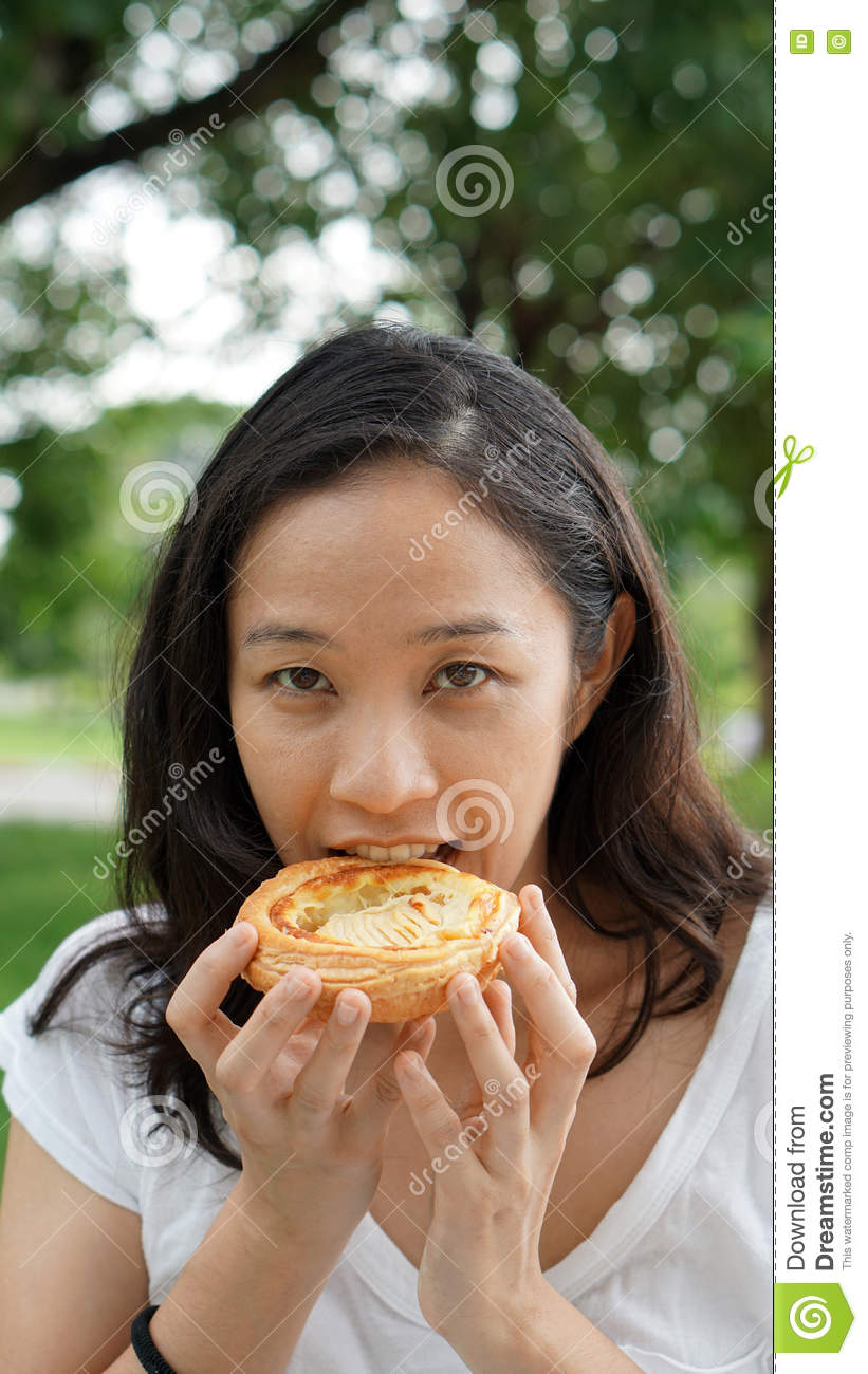 asian woman mature adult eating bread carbohydrates stock photo