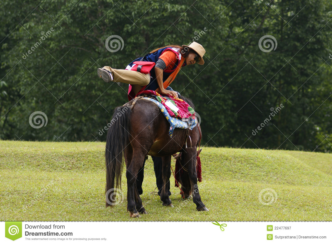 Asian woman mounting horse on grass with leafy trees in background.