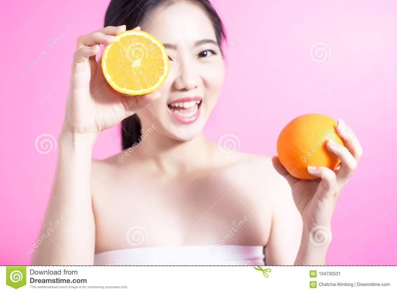 Asian woman with orange concept. She smiling and holding orange. Beauty face and natural makeup. Isolated over pink background.