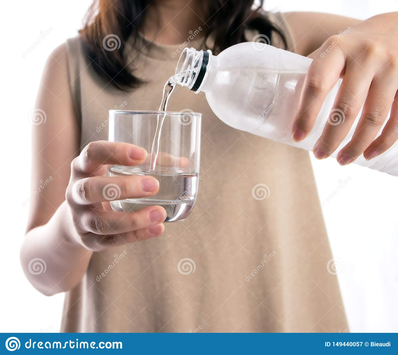 Asian woman pouring water from a plastic bottle into a glass