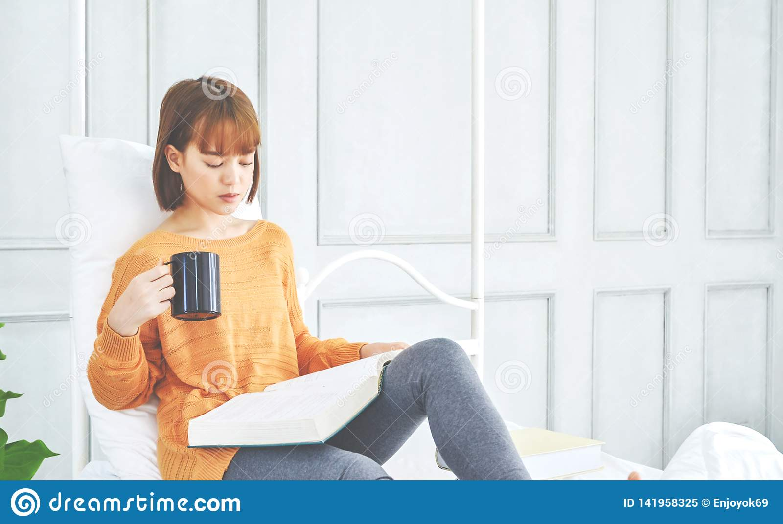 Women are reading a book holding a black glass.