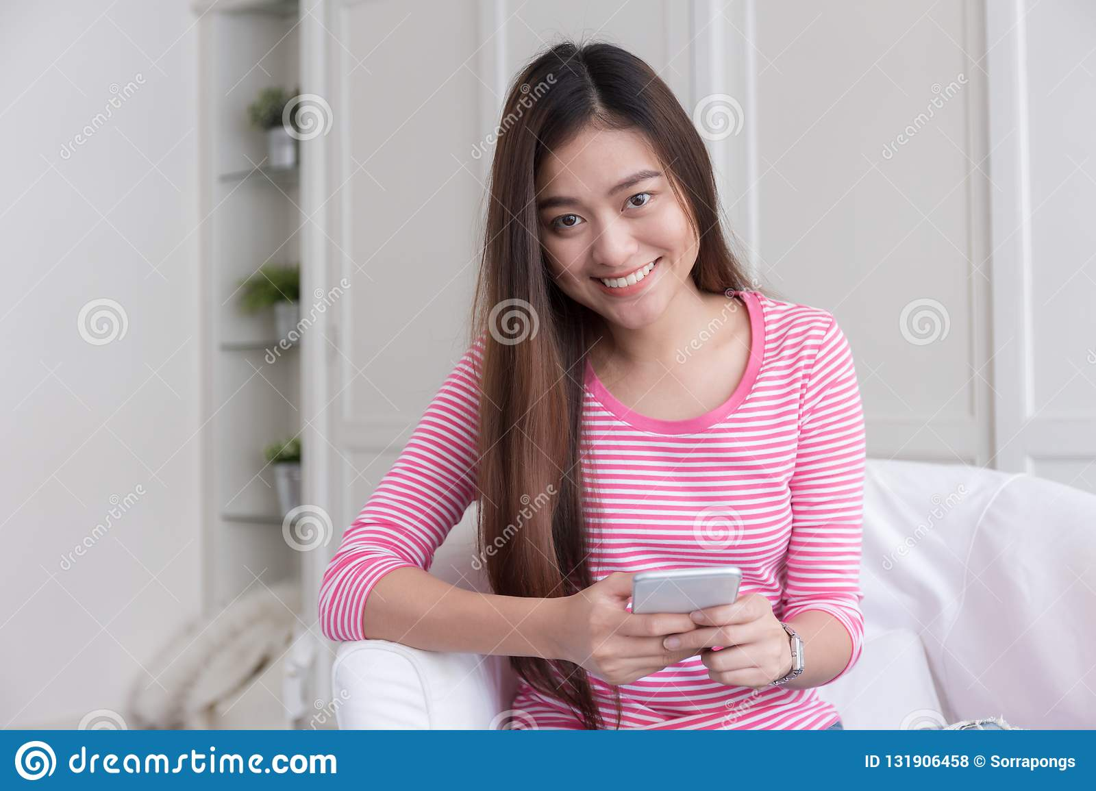 Asian woman is smiling and using smartphone on blurred background at white bedroom.