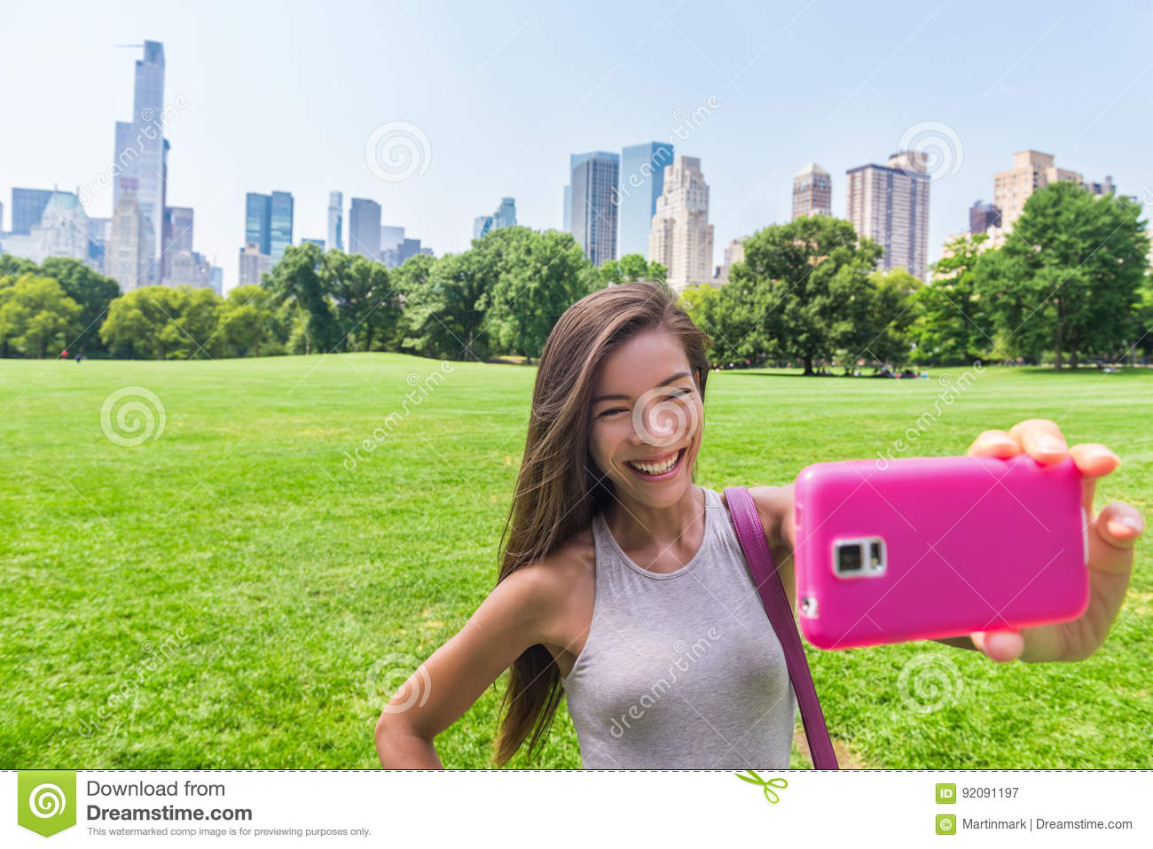 Asian woman taking phone selfie in New York city