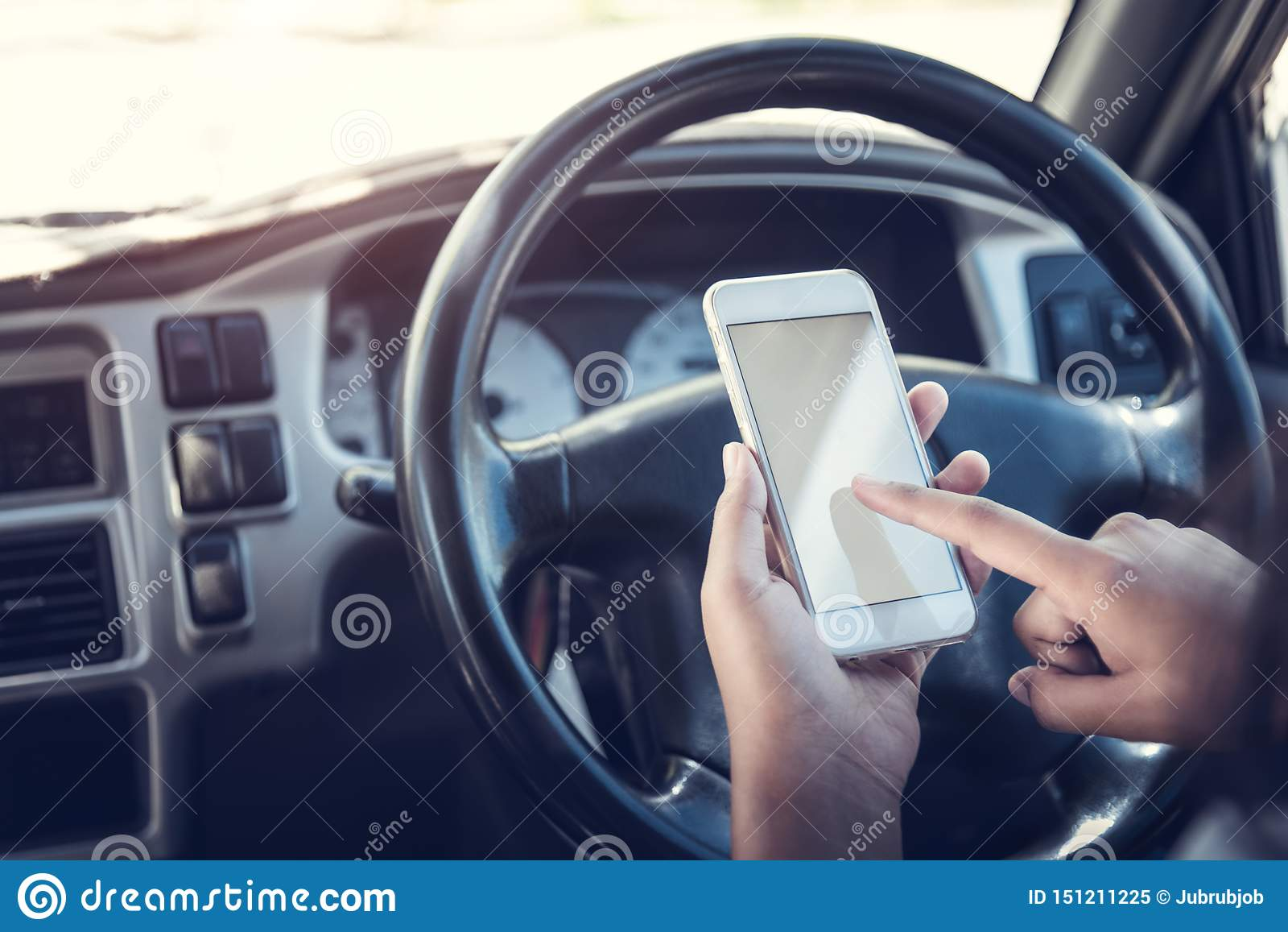 Asian woman talk by mobile calling texting and looking on a cellular phone while sitting in her car, driving under the influence,
