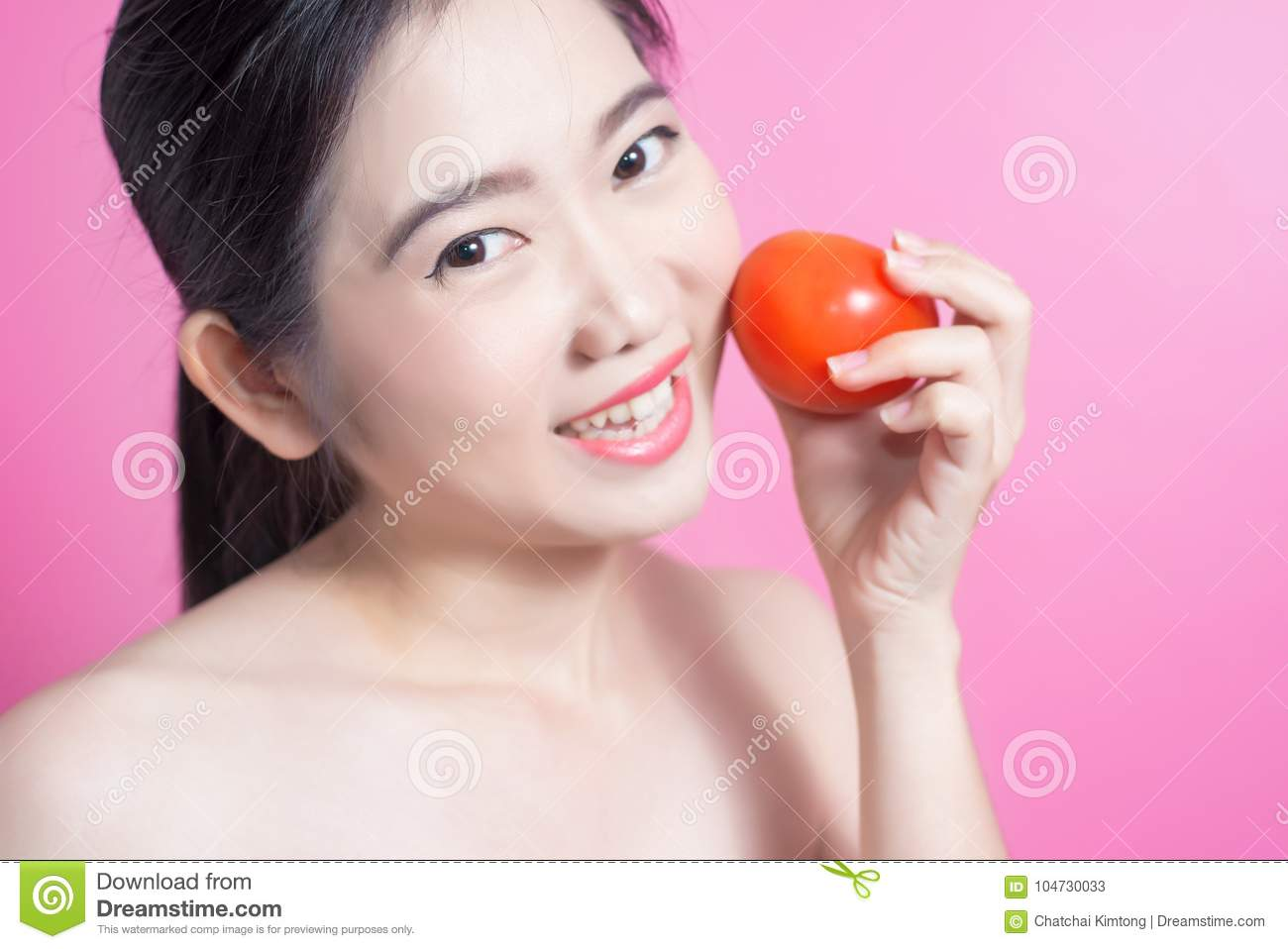 Asian woman with tomato concept. She smiling and holding tomato. Beauty face and natural makeup. Isolated over pink background.