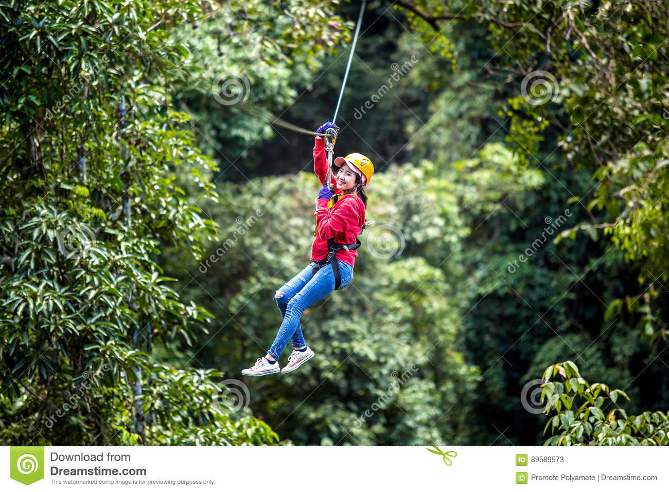 Asian woman TOURIST adult wearing casual clothes Zip Line On Focus FOREST TR
