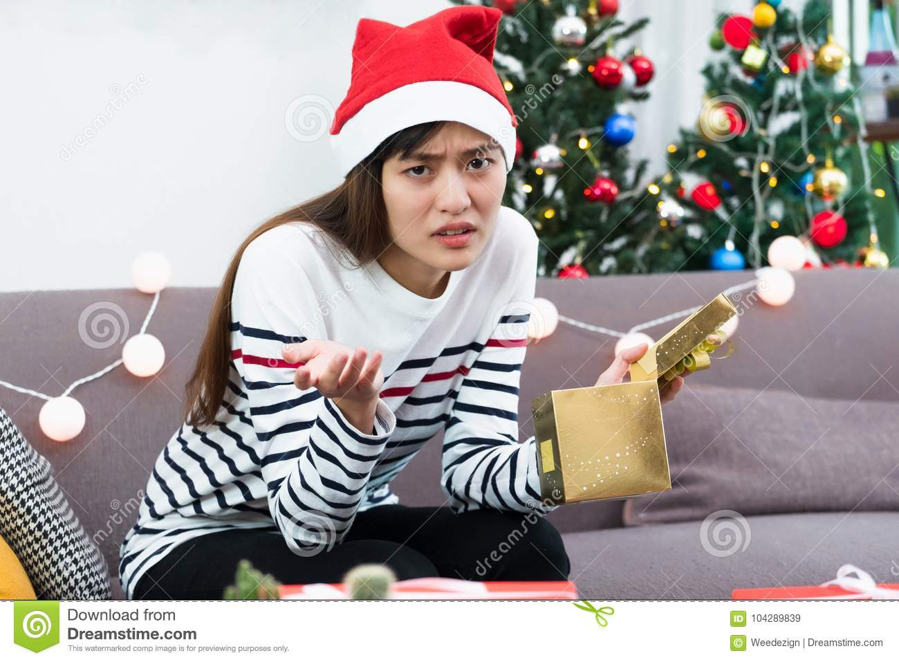 asian woman upset when open gold xmas gift box at holiday party on sofaboredom christmas party present - When Do You Open Christmas Presents