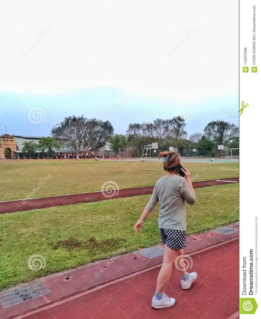 An asian woman is walking on the track of a school, and talking on the phone while walking.