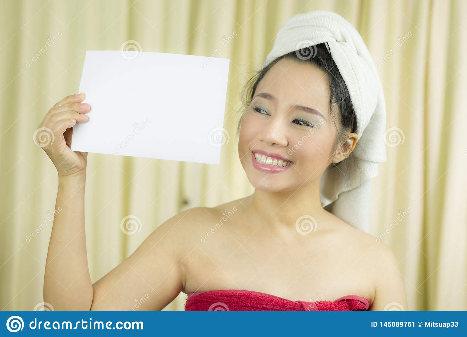 Asian woman wear a skirt to cover her breast after wash hair, Wrapped in Towels After Shower holding empty blank banner and acting