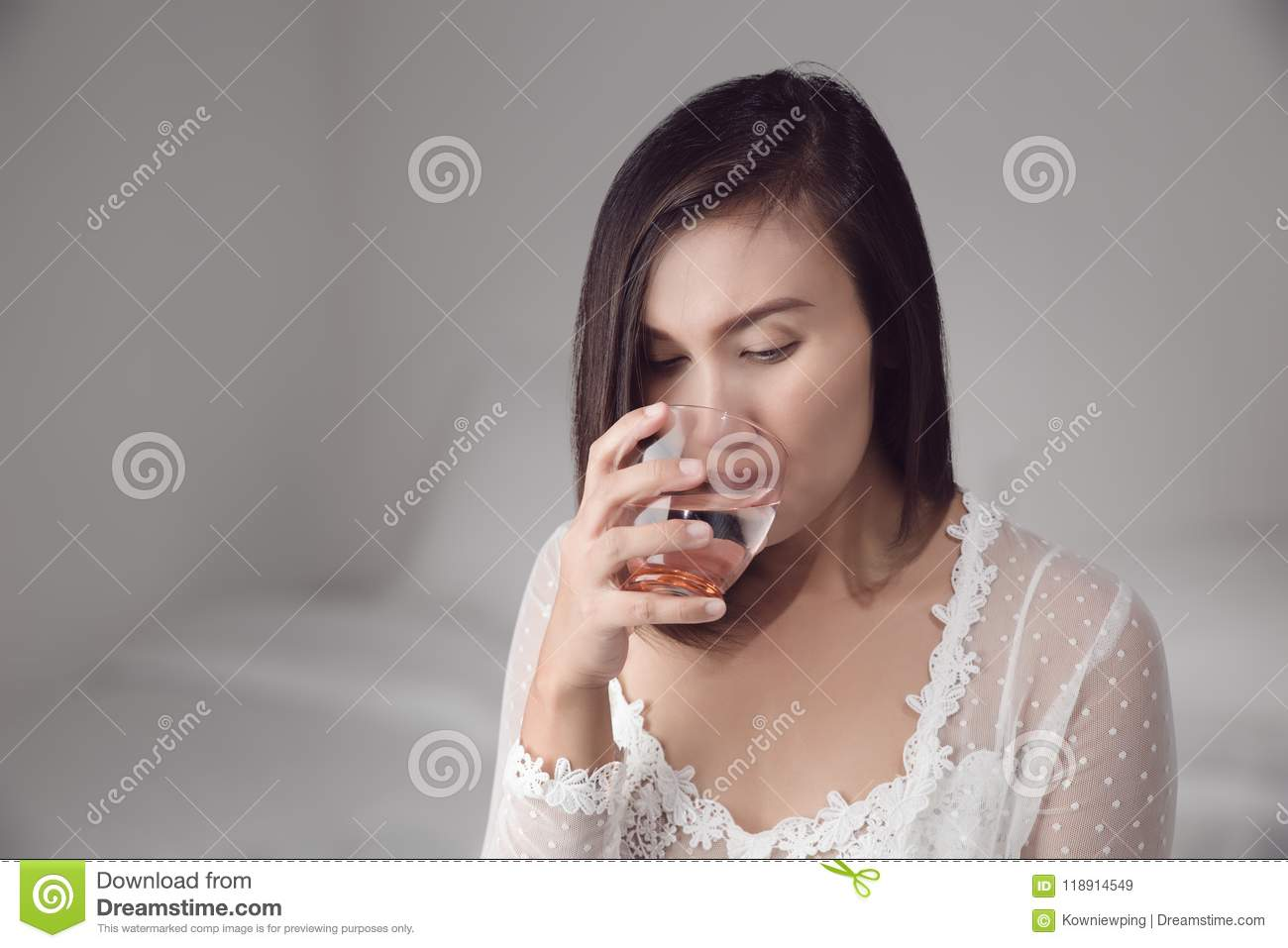 2cf198f3b6 Asian woman in white nightwear drinking water before bedtime for good health  at bedroom. Basic concepts in health and health care.