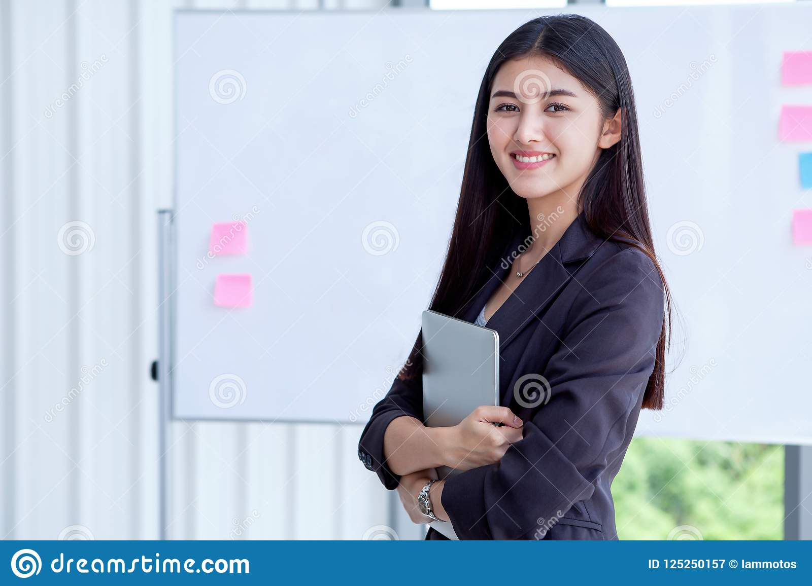 asian young business woman holding Digital tablet Computer isolated on White board background in office.smiling secretary girl wi