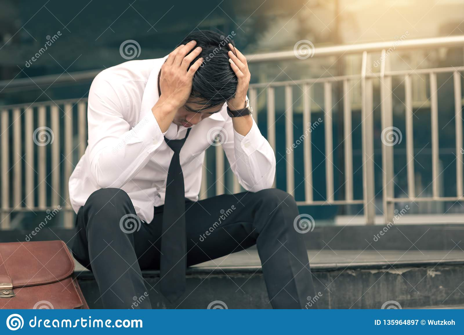 Asian young businessman stress sitting in front office with his hands covering his head against
