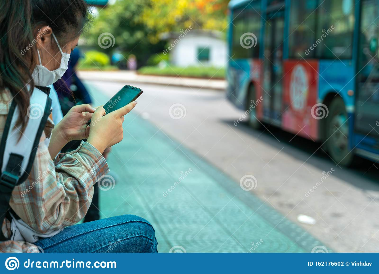 Asian Young Girl Use Smartphone Waiting For Bus At Bus