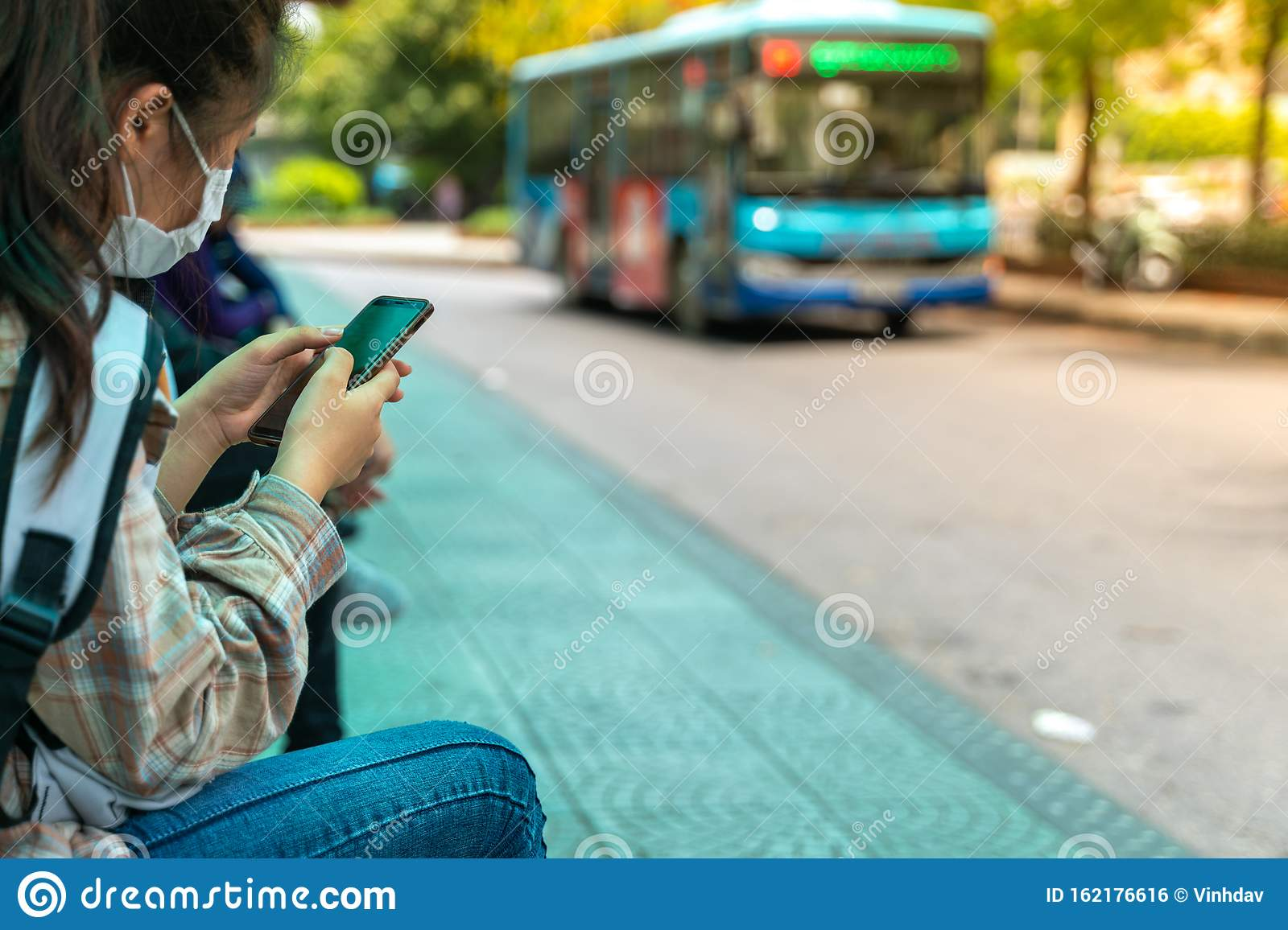 Asian People Use Smartphone Waiting For Bus At Bus Stop