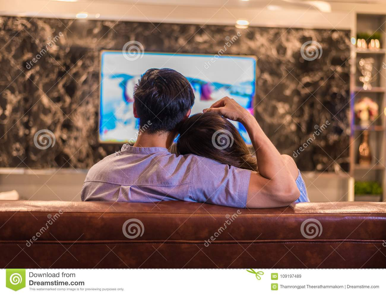 Asian young lovers watching television on sofa. Couples and Relax concept. Holiday and vacation concept. Night dating and