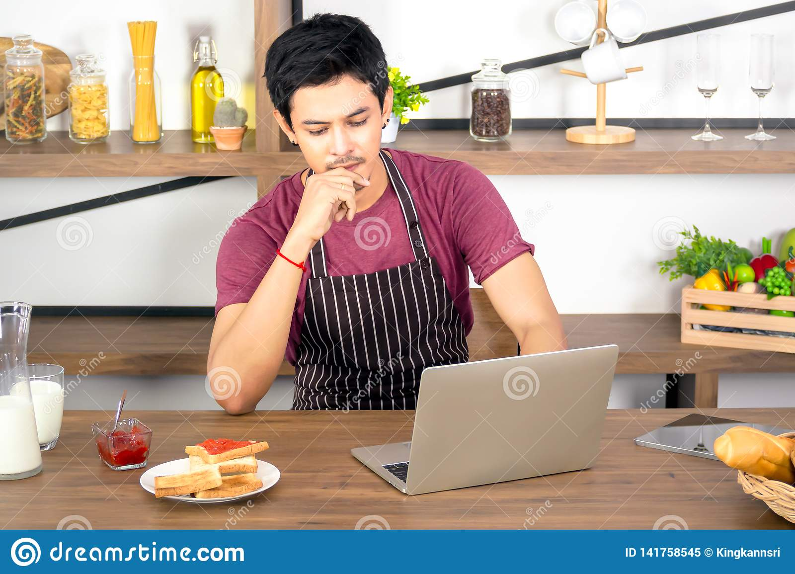 Asian young man using laptop for online working