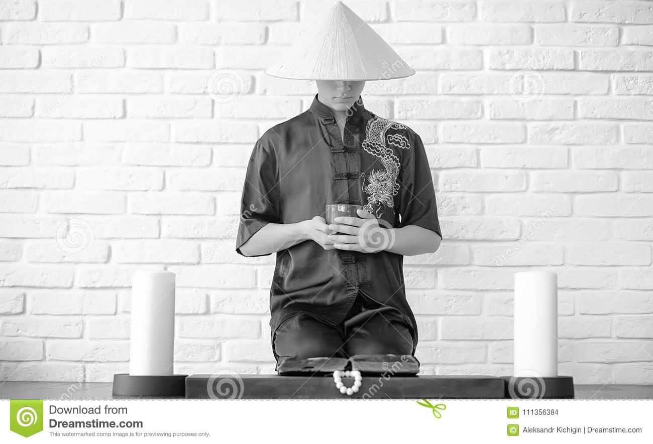 Asian novice on a white brick wall