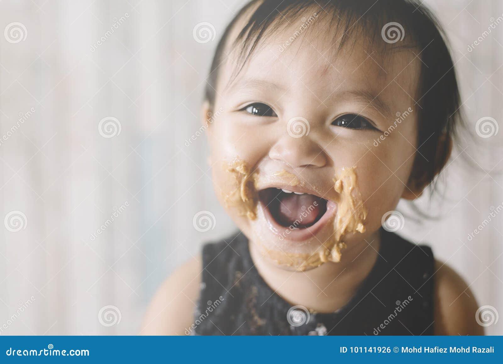 Asiatet behandla som ett barn flickan som ler med munnen och, vänder mot mycket av jordnötsmör