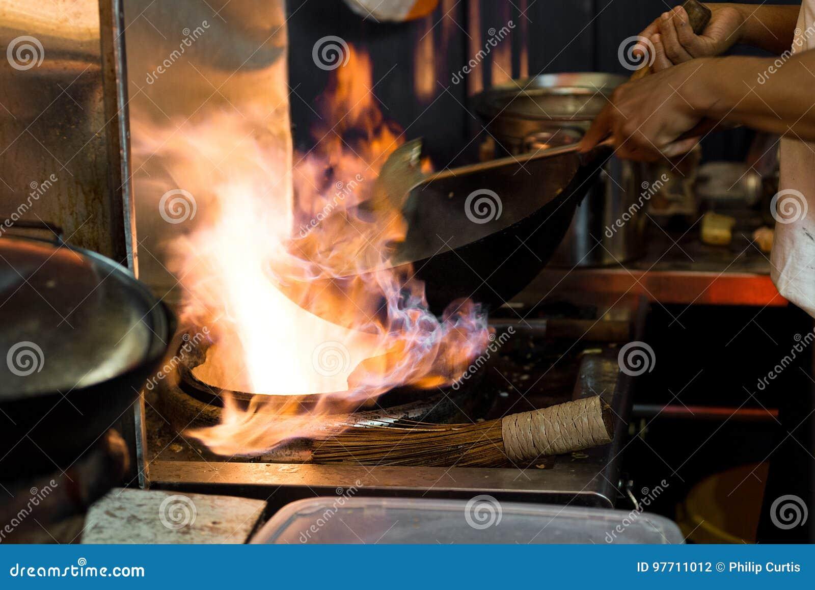 Asiatet wokar matlagning med flammor i en öppen kitc för stilgatamat