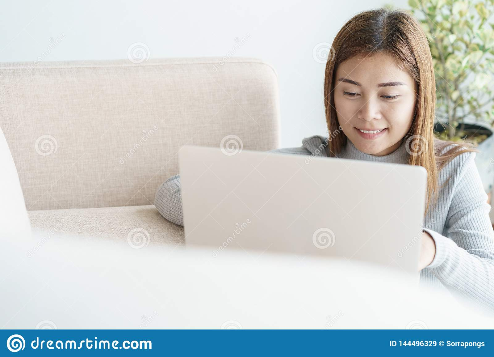 Asiatin arbeitet an Laptop im Wohnzimmer Sie sitzt auf dem Boden und Sofa ist Schreibtisch