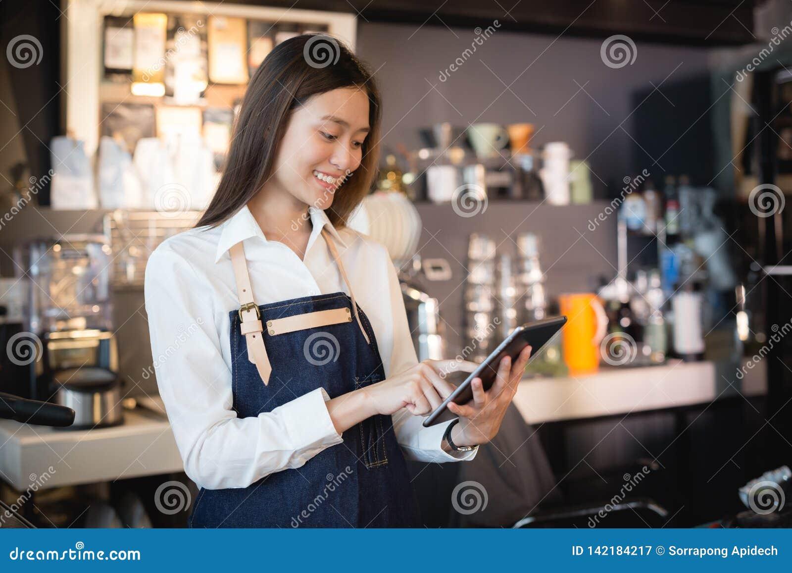 Asiatin barista, das mit Tablette in ihrer Hand, weibliche Angestellte lächelt, nehmen Bestellungen von den on-line-Kunden entgeg