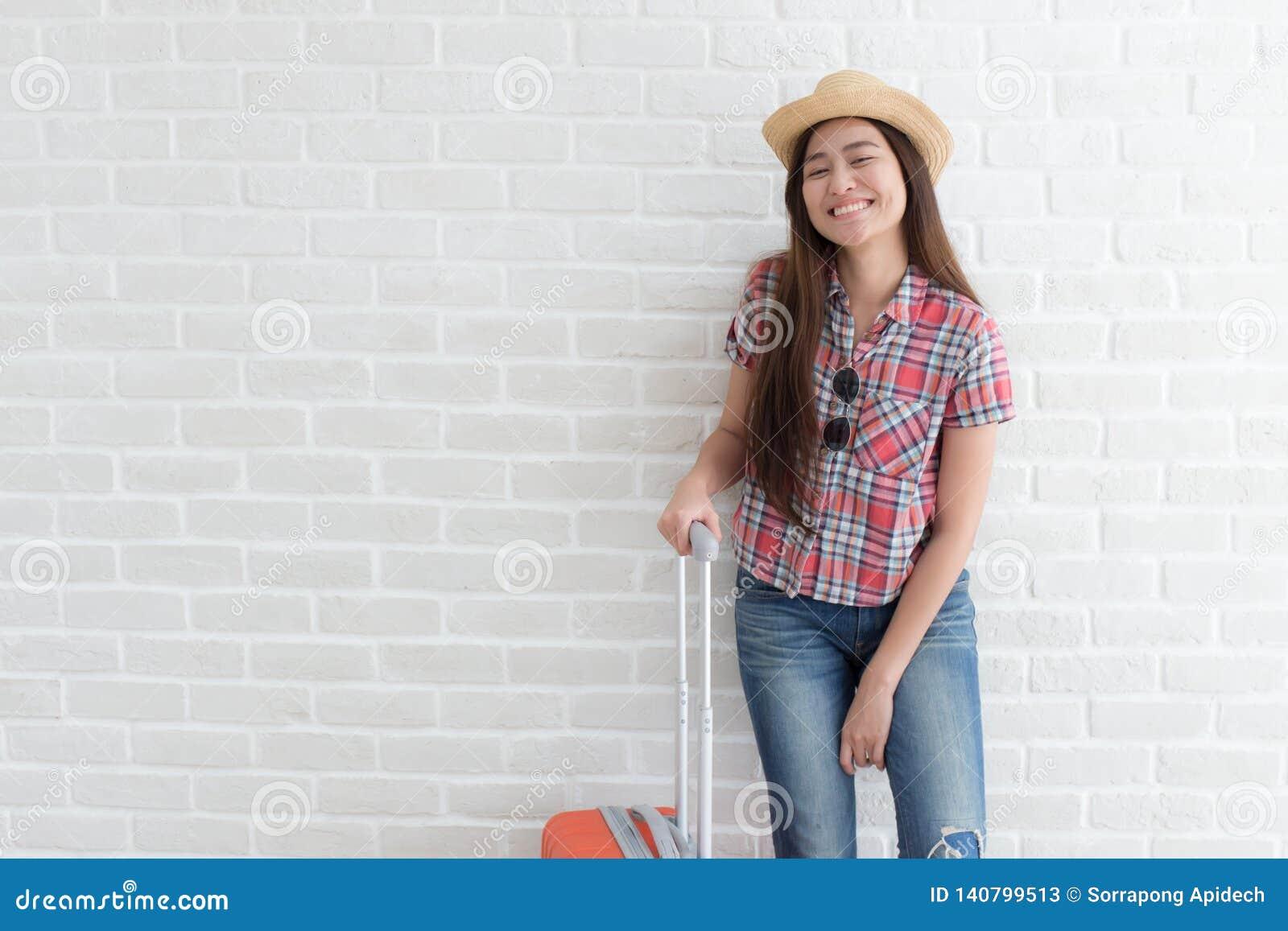 Asiatin bereiten vor sich, auf weiße Backsteinmauer, Lebensstil und Tourismus zu reisen
