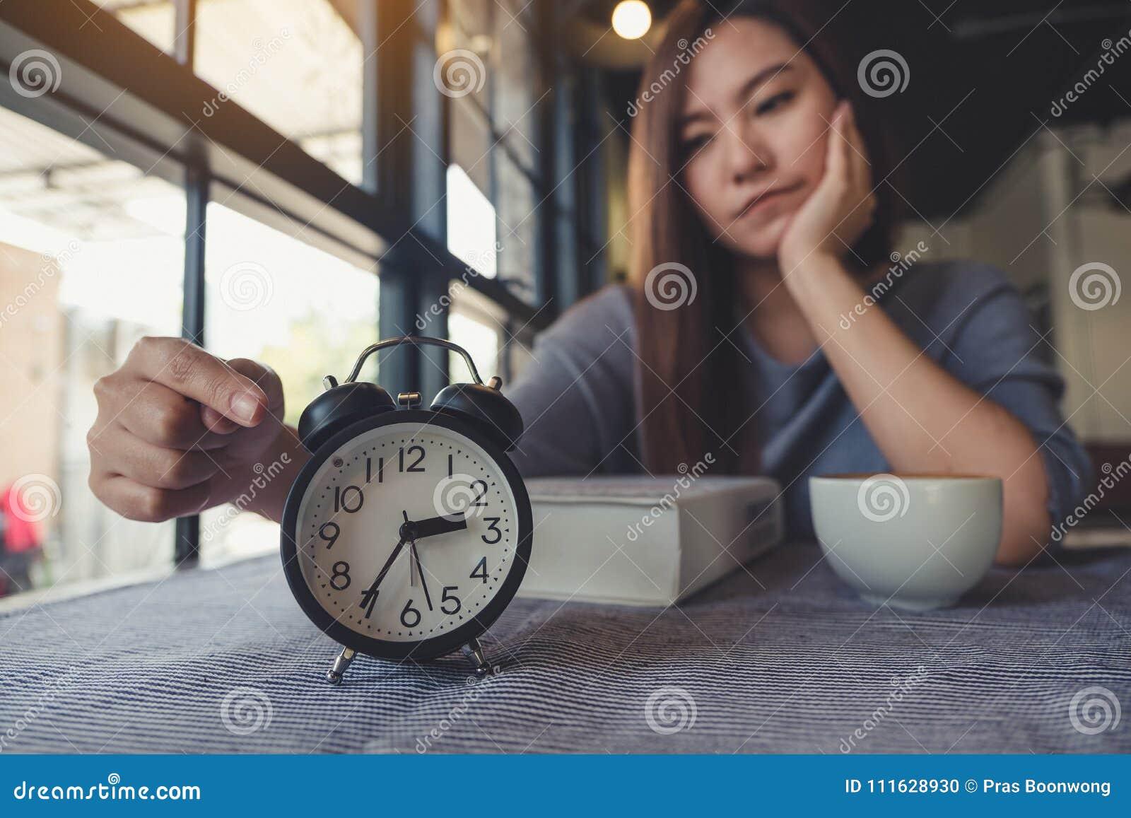 Asiatin, die auf eine schwarze Uhr mit dem Gefühl beim Warten auf jemand gebohrt zeigt