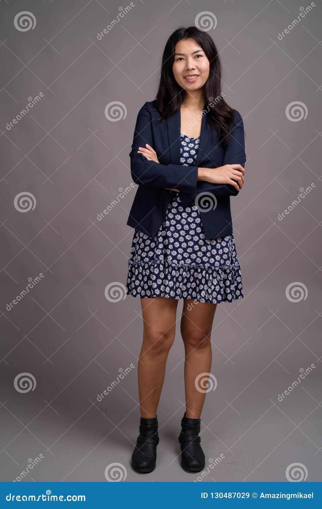 asiatin, die blaues kleid und wolljackenstrickjacke gegen