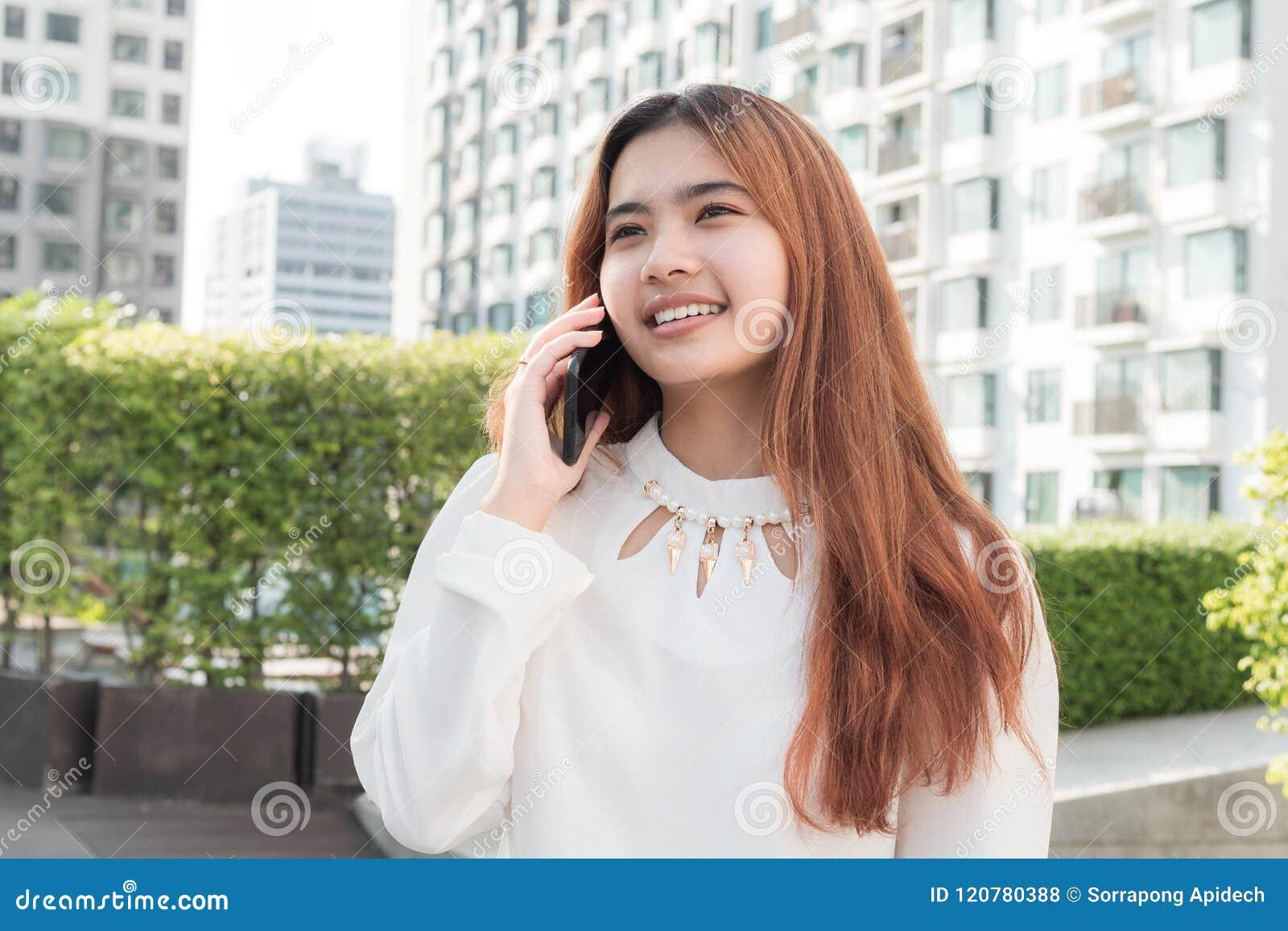 Asiatin, die intelligentes Telefon auf unscharfem Hintergrund von residenti verwendet