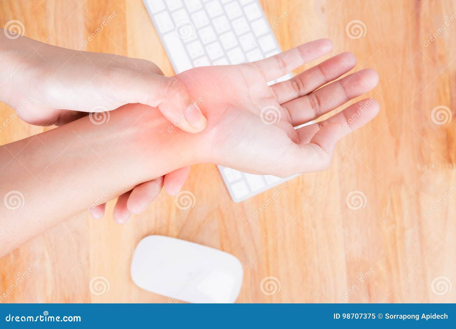 Asiatin, die schmerzliche Hand massiert