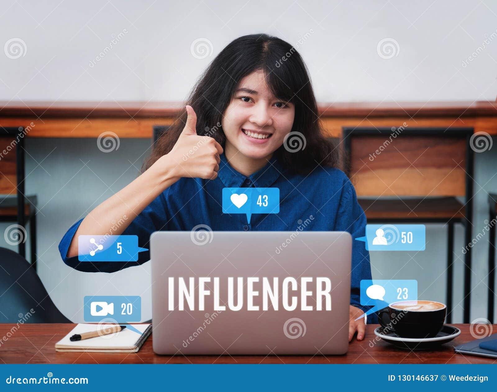 Asiatin influencer Daumen oben und Lächeln unter Verwendung des Laptops mit cof