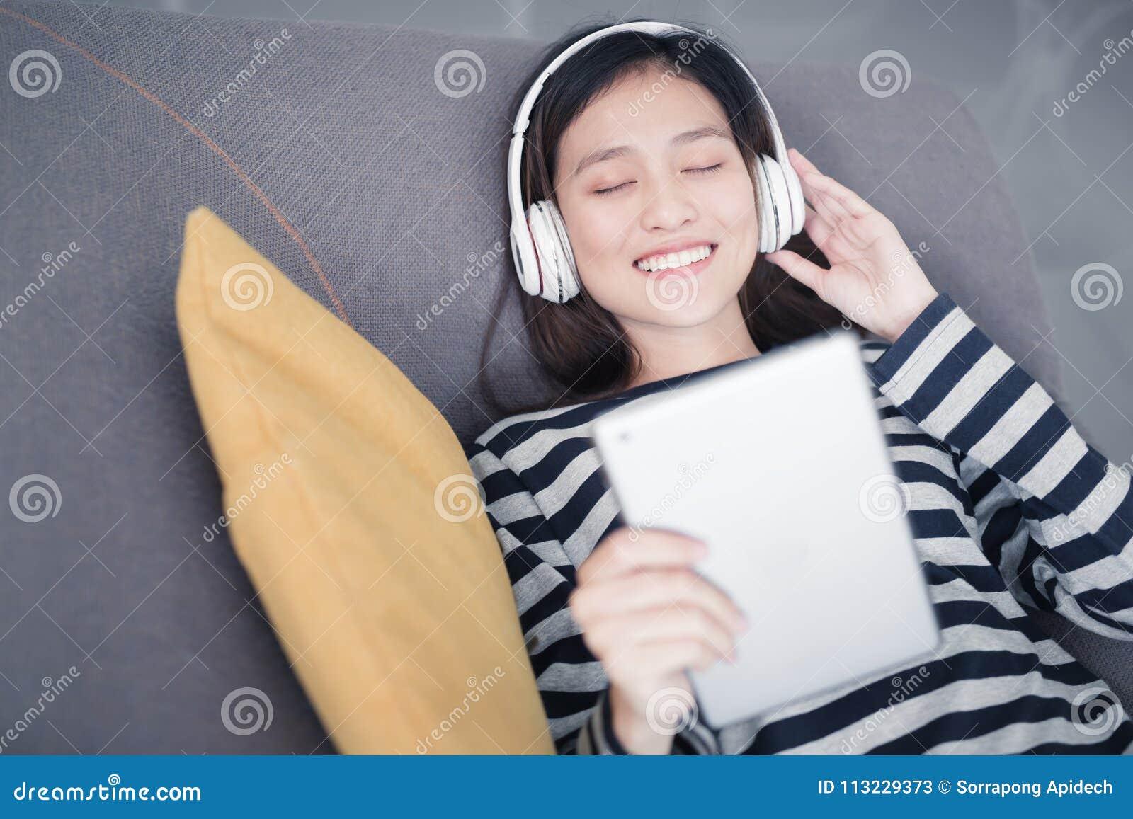 Asiatin ist das Stillstehen und hört Musik auf Sofa mit Kopfhörer