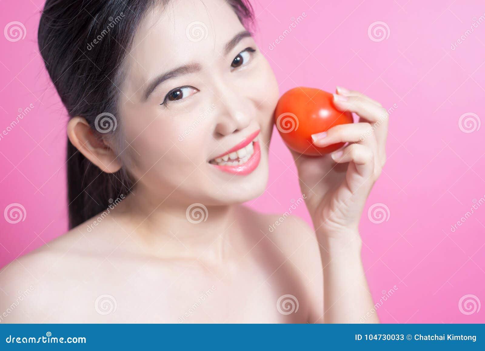 Asiatin mit Tomatenkonzept Sie lächelnd und Tomate halten Schönheitsgesicht und natürliches Make-up einfach für Sie ändern Sie Fa
