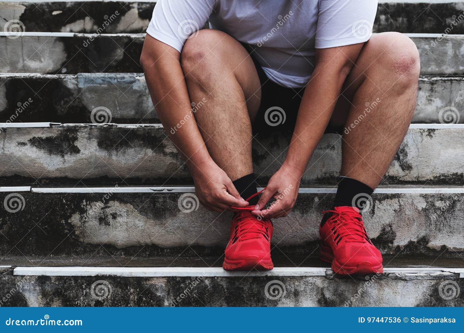 Asiatique Guy Tying Running Shoe, se préparant au fonctionnement au poids perdant