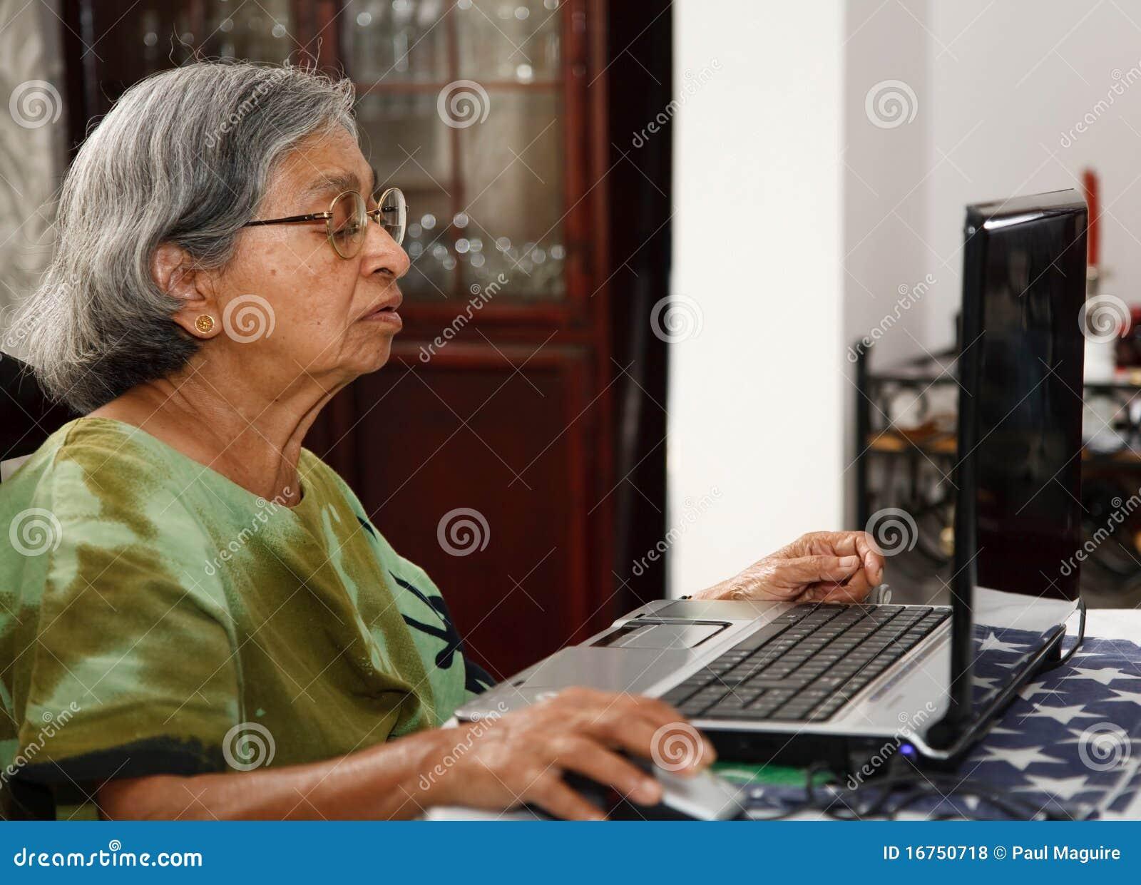 Asiatische alte Frau, die Computer verwendet