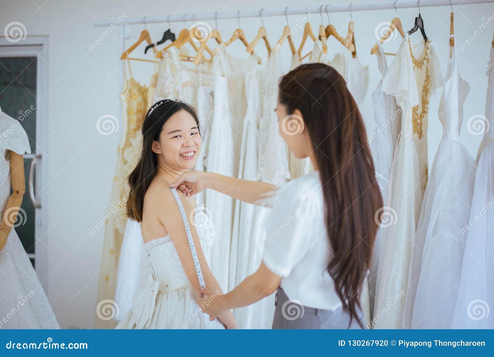 Asiatische Braut, die auf Hochzeitskleid, dem Frauendesigner in Mode machen Studio der Anpassung, glücklichem und das Lächeln ver