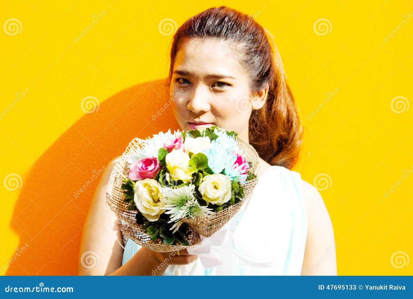 Asiatische Dame im Kleiderreihen-Griffblumenstrauß